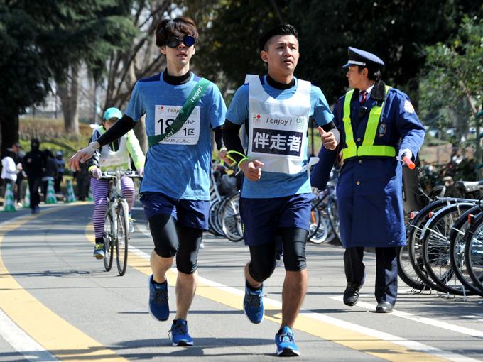 【1区】アイマスクを装着して走る、御茶ノ水男子のしいはしジャスタウェイ(左)と伴走者のおもしろ佐藤