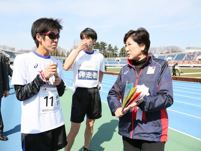 1区を走り終え、小池知事からインタビューを受ける米岡聡選手と伴走の奥村直樹選手(東京わくわくエンジョイ)