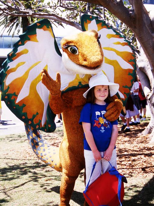"""エリマキトカゲのマスコット「Lizzy(リジー)」。""""襟巻き""""の部分は緑色と金色で、オーストラリアをかたどっており、体の黄土色は大地の色を表している。また、Lizzyの力強さ、決意、姿勢は、競技に参加するすべてのパラリンピック選手を表現している。"""