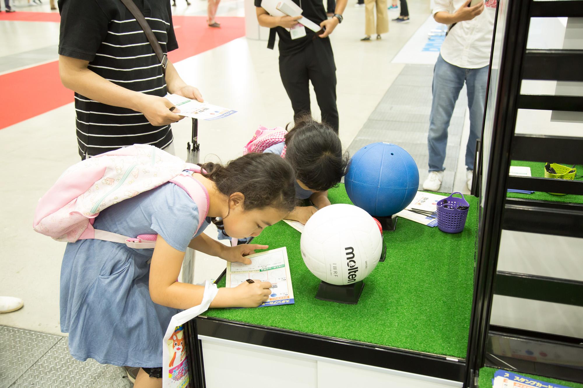 パラスポーツの道具を実際に触れて答えるクイズラリーに参加する子どもたち